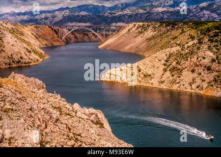 Maslenica meer Autobahnbrücke in Kroatien auf der Autobahn A1, die die Meerenge Novsko Zdrilo mit einem einsamen Speedboot und flankiert von Velebit - Stockfoto