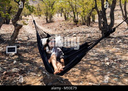 Frau Entspannen in der Hängematte - Huab unter Leinwand, Damaraland, Namibia, Afrika - Stockfoto