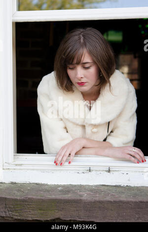 Eine Frau mit roten Lippenstift, trägt einen weissen Fell Jacke und eine Perlenkette, durch ein Fenster. Savannah, Georgia, USA - Stockfoto