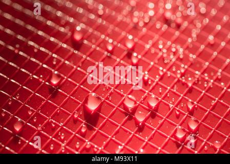 Wassertropfen auf rote Farbe Kunststoff Hintergrund Textur - Stockfoto