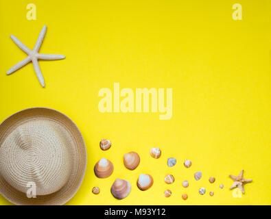 Sommer Hut und eine Auswahl an Muscheln und Seesterne, auf gelbem Hintergrund. Blick von oben. Sommer Konzept. Platz für Kopieren. - Stockfoto