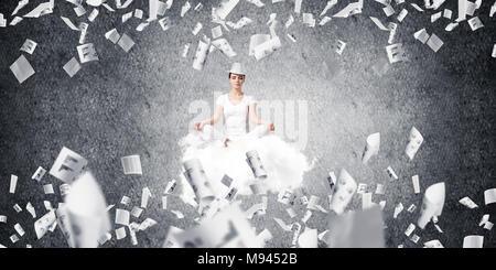 Frau in weißen Kleidern halten die Augen geschlossen und während der Meditation auf Flying Cloud unter fliegende Papiere mit dunklen Wand auf Hintergrund konzentriert - Stockfoto