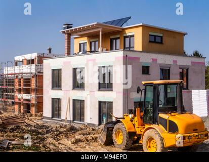 Ein neues Gebäude neben einem Shell in einem Baustellenbereich mit einem Radlader im Vordergrund. - Stockfoto