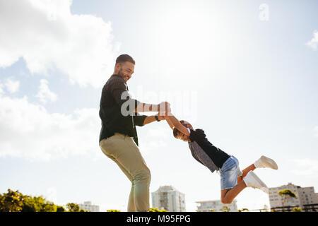 Fröhlicher Mann spielt mit seinem Sohn an einem Park. Vater sein Kind heben in der Luft durch seine Hände. - Stockfoto