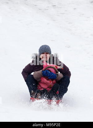 Großmutter schaut erschrocken und Grand-Tochter deckt Ihre Augen beim Schlittenfahren in Québec, Kanada - Stockfoto