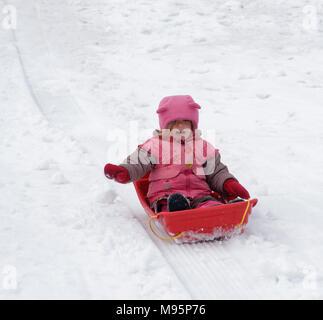 Ein kleines Mädchen (3 Jahre alt) Rodeln im kanadischen Quebec - Stockfoto