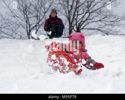 Ein kleines Mädchen (3 Jahre alt) Rodeln im kanadischen Quebec mit Mama darüber hinaus, auf. - Stockfoto