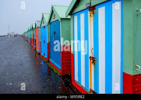 Brighton Seafront vierzig Badekabinen, die Hütten haben mehrfarbige Türen in einer geraden Linie auf eine konkrete Promenade der Himmel grau ist der nächstgelegene Strand h - Stockfoto