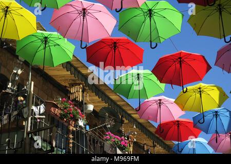 Fliegende Regenschirme neben städtischen Balkon mit Blumenkästen im Sommer City Festival - Stockfoto