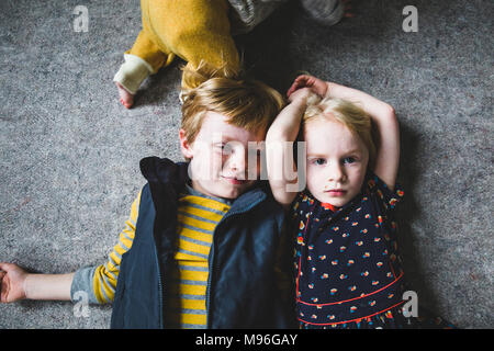 Bruder und Schwester nebeneinander verlegen Stockfoto