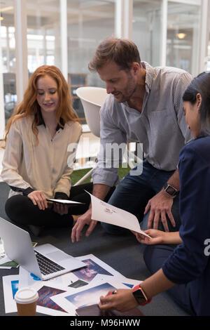 Kollegen diskutieren über Laptop - Stockfoto