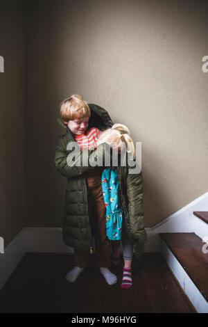 Junge und Mädchen in überdimensionalen Jacke Stockfoto