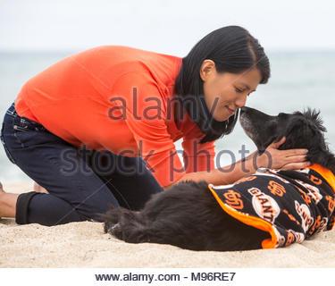 Junge asiatische Frau kniend Gesicht im Sand mit Ihrem älteren Hund zu Gesicht - Stockfoto