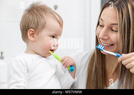 Glückliche Mutter Lehre ihren Sohn, wie Zähne im Bad zu Bush - Stockfoto
