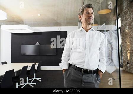 Portrait von Reifen Geschäftsmann gegen Glasscheibe in modernen Konferenzraum schiefen - Stockfoto