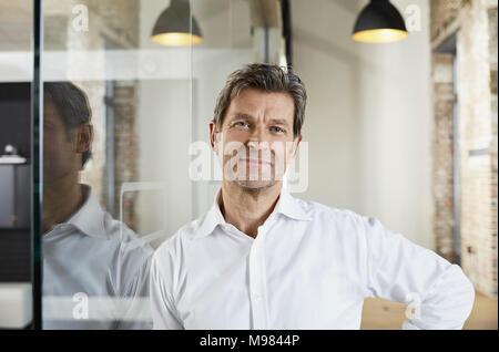 Portrait von lächelnden Geschäftsmann lehnte sich gegen Glasscheibe - Stockfoto