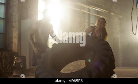 Fit athletische Frau Aufzüge Reifen unter Aufsicht von Ihrem Partner/Trainer, als Teil ihrer Cross Fitness/Bodybuilding Fitness Training. Sie gibt hohe Fünf - Stockfoto