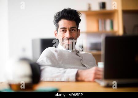 Portrait von entspannt Geschäftsmann am Schreibtisch - Stockfoto