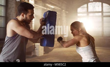 Athletische Frau Züge ihre Schläge auf einen Boxsack, dass Ihr Partner/Trainer hat. Sie ist professionelle Kämpfer und arbeitet in einem Hardcore Gym. - Stockfoto