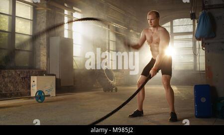 Starke muskuläre Shirtless Sportler arbeitet hart, mit Kampf Seile als Teil seines Kreuzes Fitness Training Programm. Er bedeckt in Schweiß - Stockfoto
