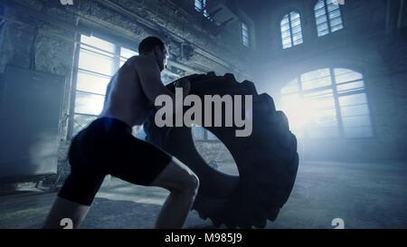 Starker, muskulöser Mann Aufzüge Reifen als Teil seines Kreuzes Fitness Routine. Er bedeckt in Schweiß und arbeitet in einer verlassenen Fabrik umgebaut in ein Fitnessstudio. - Stockfoto