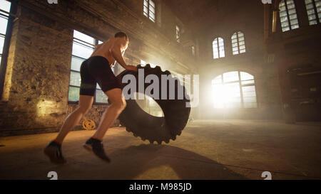 Starker, muskulöser Mann Aufzüge Reifen als Teil seines Kreuzes Fitnessprogramm. Er bedeckt in Schweiß und arbeitet in einer verlassenen Fabrik umgebaut in ein Fitnessstudio. - Stockfoto