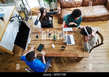 Ansicht von Kollegen hören von Musik an den hölzernen Tisch im Büro - Stockfoto