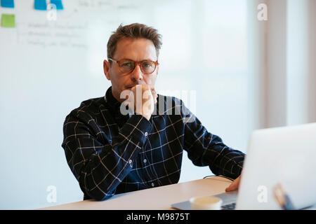 Porträt von Ernst Kaufmann mit Laptop auf dem Schreibtisch im Büro - Stockfoto
