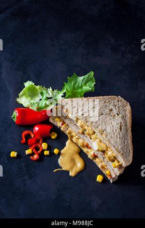 Chicken Sandwich mit Mais, Peperoni und Currysauce auf dunklem Boden - Stockfoto