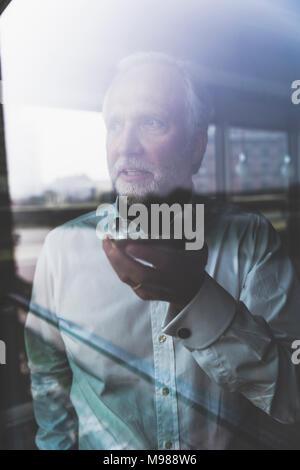 Portrait von Reifen Geschäftsmann am Fenster mit Handy - Stockfoto