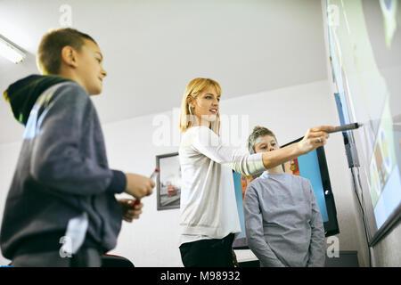 Lehrer mit Schülern im Unterricht am interaktiven Whiteboard