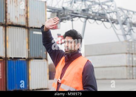 Mann mit Warnweste am Container Hafen arbeiten - Stockfoto
