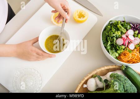 Junge Frau bereitet einen frischen Salat Dressing - Stockfoto