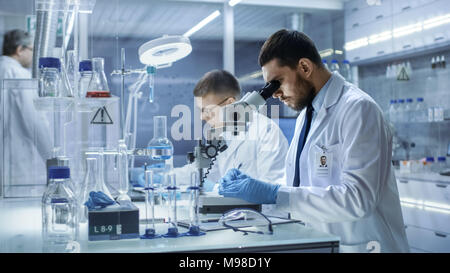In einem modernen Labor zwei Wissenschaftler Experimente durchführen. Chief Research Scientist passt Muster in eine Petrischale und sieht es in Mikroskop. - Stockfoto