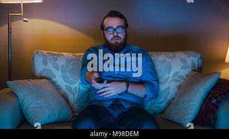 Porträt der Mann sitzt auf einem Sofa in seinem Wohnzimmer, Popcorn essen und Fernsehen. Standleuchten eingeschaltet sind. - Stockfoto