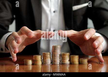 Unternehmer, die für eine der Münzen Stapel - Stockfoto
