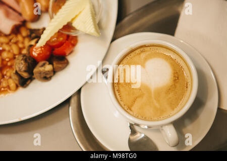 Ein traditionelles, englisches Frühstück. Eine Tasse Kaffee mit Cappuccino ist daneben. National Food. Welt-berühmte Gericht, das jeden Morgen serviert wird. Stockfoto