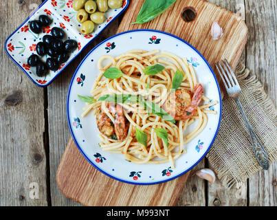 Pasta Spaghetti mit Pesto rоssо, Garnelen, Basilikum und Knoblauch auf einer hölzernen Hintergrund. Selektiver Fokus, Ansicht von oben.