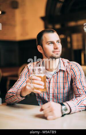 Hübscher junger Mann trinken helles Bier in einem Pub. - Stockfoto