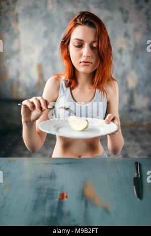 Weibliche Person gegen die Platte mit einer Scheibe von Apple - Stockfoto