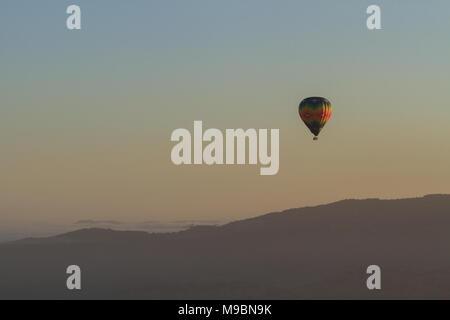 Einsame Heißluftballon über die Berge in der Morgendämmerung - Stockfoto