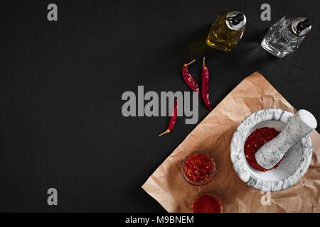 Getrocknete und zerkleinerte rote Chili Pfeffer in Stein, Mörtel auf schwarzem Hintergrund. Kopieren Sie Platz. Ansicht von oben. Immer noch leben. Flay legen - Stockfoto