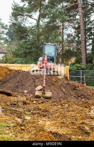 Große orange schwere Anlage mechanische Bagger auf einem Erdhügel auf einem neuen suburban Wohnentwicklung Baustelle geparkt - Stockfoto