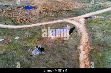 Abgebrochene Stein Bauernhof Hütte in der Nähe von Crackenback in Thredbo Valley der schneebedeckten Berge, Australien. Luftaufnahme über das Haus und in der Nähe nicht abgeschottete Road w - Stockfoto