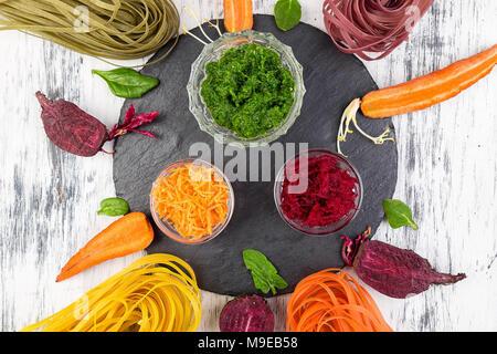 Farbige rohes Gemüse vegetarische Pasta mit roten Rüben, Karotten und Spinat. Zutat für vorbereiten. - Stockfoto
