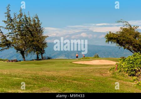 Ein Paar auf einem Golfkurs auf Maui, Hawaii, USA. Jenseits der Golfplatz ist der Pazifische Ozean und erfolgsabhängige Fuß hohen Puu Kukui, erste Maui's Vulkan. - Stockfoto