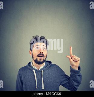 Junge casual hipster Mann mit Bart auf der Suche oben in erfolgreiche Idee auf Grau. - Stockfoto