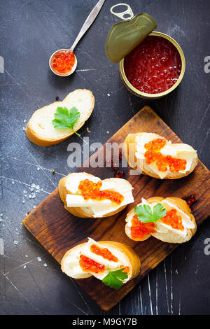 Festliche Snack. Sandwiches mit rotem Kaviar, auf dunklen konkreten Hintergrund isoliert. - Stockfoto