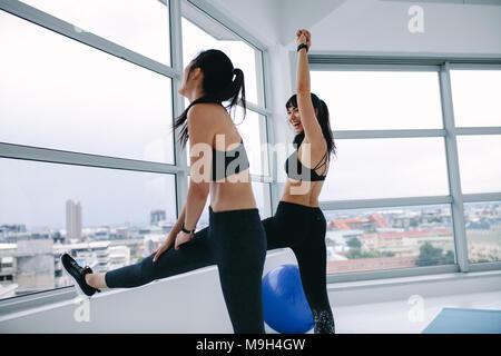 Zwei junge Frauen, Stretching Training gegen ein Fenster und lächelnd. Weibliche Freunde zusammen trainieren im Fitnessstudio. - Stockfoto