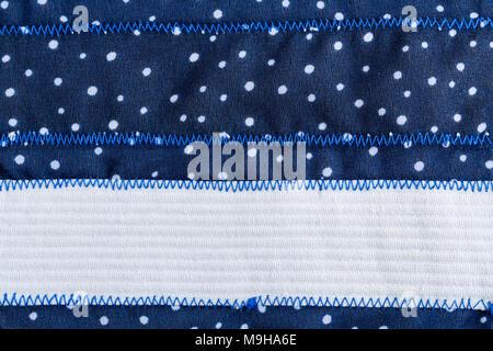 Background aus blauem Stoff mit weißen Punkten, Zick-Zack-Stich und mit einem weißen Tuch streifen. - Stockfoto